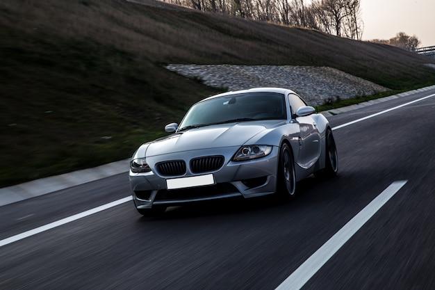 Vista frontal del coche deportivo color gris metálico en la carretera.