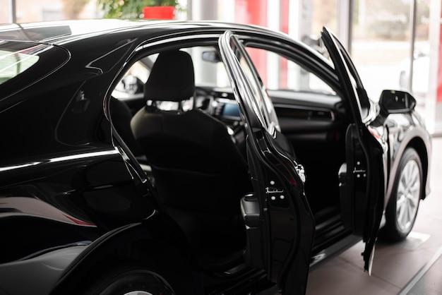 Vista frontal coche nuevo negro con puertas abiertas
