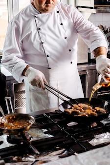 Vista frontal cocinar carne frita dentro de una sartén redonda en la cocina