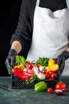 Vista frontal cocinera con canasta llena de verduras frescas en color oscuro comida ensalada cocina cocina