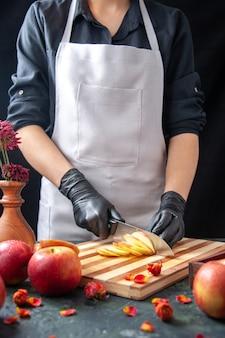 Vista frontal cocinera cortando manzanas en una ensalada de dieta oscura comida comida jugo de frutas exóticas