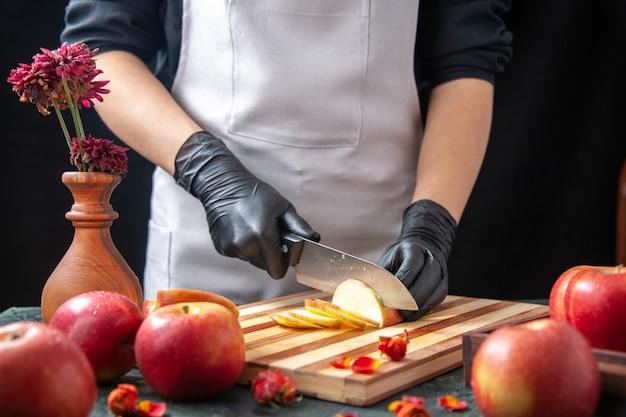 Vista frontal cocinera cortando manzanas en ensalada de dieta vegetal oscura comida comida bebida fruta
