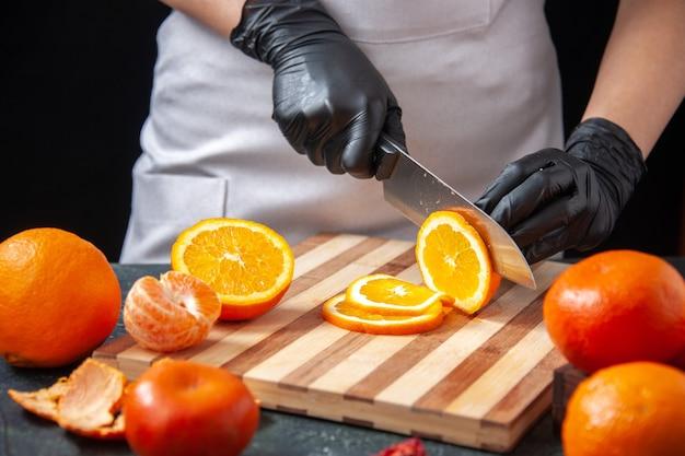Vista frontal cocinera cortando naranja en una bebida vegetal oscura comida saludable comida trabajo fruta dieta ensalada