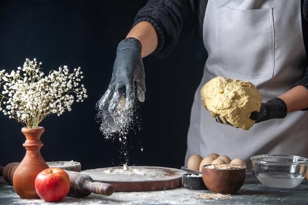 Vista frontal cocinera extendiendo la masa con harina en la oscuridad trabajo masa pastelería cocina hotcake cocina panadería huevo
