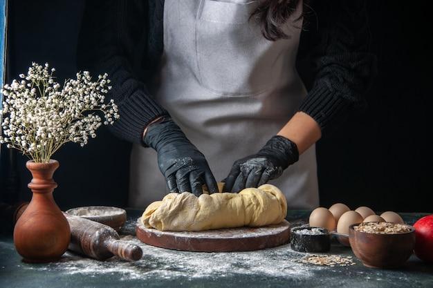 Vista frontal cocinera extendiendo la masa en el oscuro trabajo de pastelería horno de tarta de panadería hotcake cruda