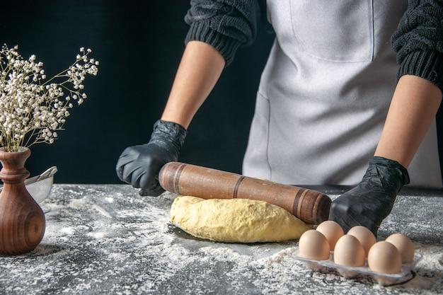 Vista frontal cocinera extendiendo la masa con rodillo en la masa oscura trabajo de huevo panadería hotcake pastelería cocina cocina