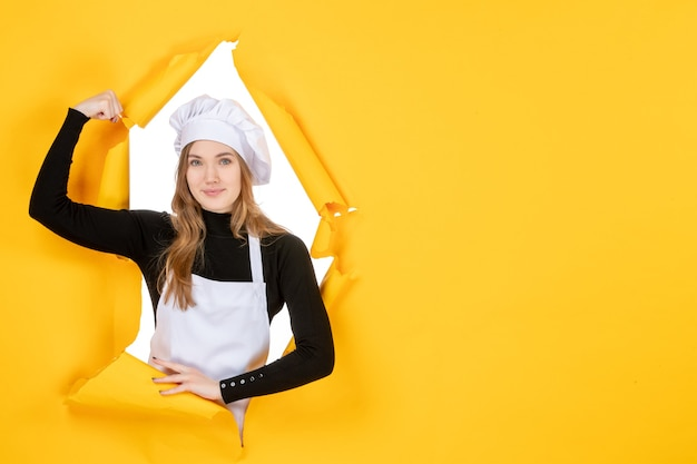 Vista frontal cocinera flexionando y sonriendo en amarillo emoción papel de color trabajo cocina sol comida foto