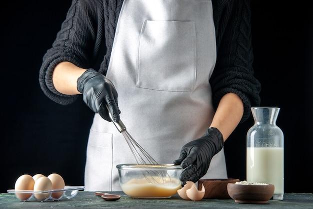 Vista frontal cocinera mezclando huevos y azúcar para masa en pasteles oscuros pastel pastel trabajador masa trabajo cocina hotcakes