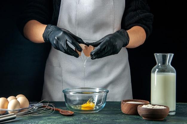 Vista frontal de la cocinera rompiendo los huevos para la masa en el trabajo de pastelería oscuro pastel pastel panadería trabajador cocina