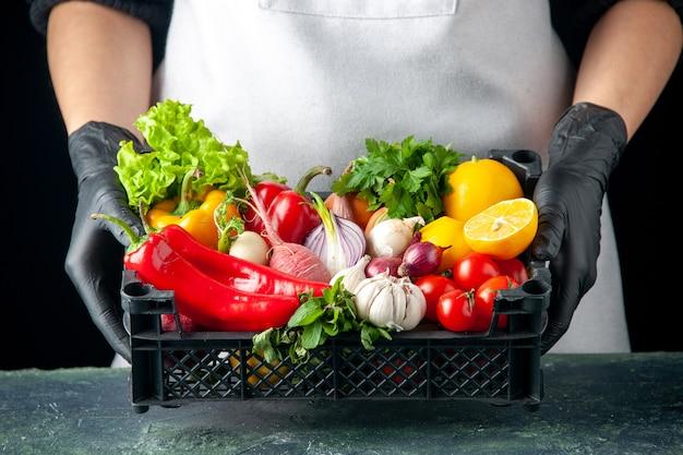 Vista frontal cocinera sosteniendo la cesta con verduras frescas en alimentos oscuros cocinando ensalada de color cocina cocina