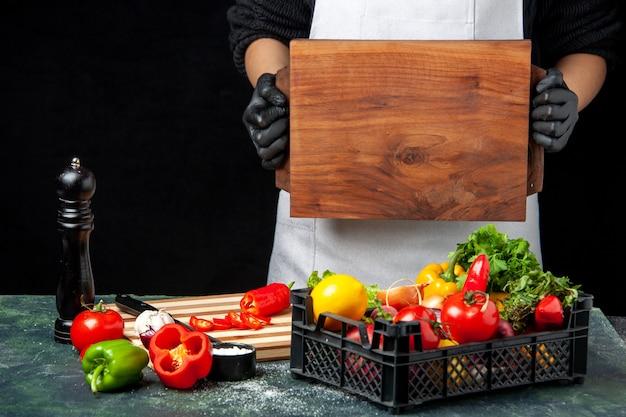 Vista frontal cocinera sosteniendo un escritorio de madera con verduras frescas en la mesa en la comida de cocina de cocina de ensalada de color oscuro