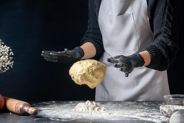 Vista frontal cocinera sosteniendo la masa en la masa oscura huevo trabajo panadería hotcake cocina cocina