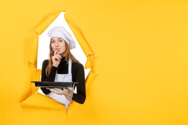 Vista frontal cocinera sosteniendo pan negro con galletas en amarillo emoción sol comida foto trabajo cocina cocina color