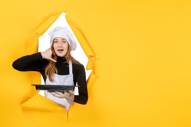 Vista frontal cocinera sosteniendo pan negro con galletas en amarillo emoción sol comida foto trabajo cocina color