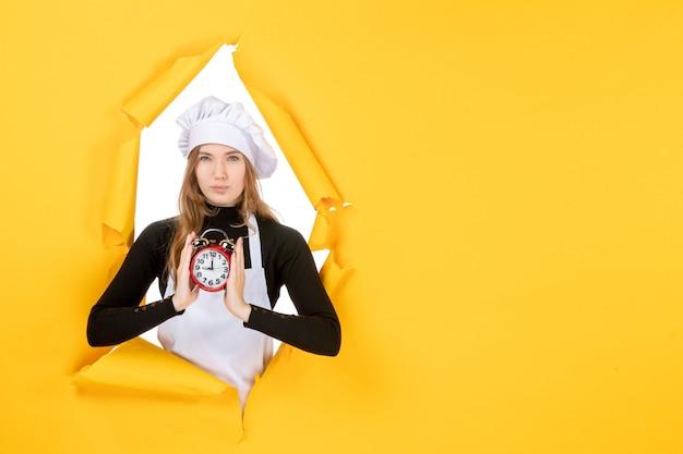 Vista frontal cocinera sosteniendo el reloj en color amarillo foto trabajo cocina cocina sol comida emoción tiempo