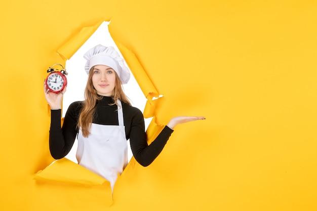 Vista frontal cocinera sosteniendo relojes en amarillo foto comida color emoción trabajo tiempo sol