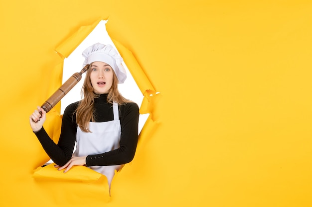 Vista frontal cocinera sosteniendo rodillo en color amarillo cocina trabajo cocina alimentos sol fotos