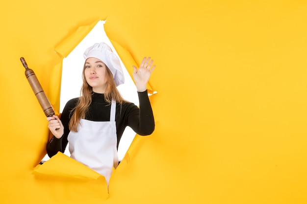 Vista frontal cocinera sosteniendo un rodillo sobre color amarillo comida cocina trabajo cocina foto emoción