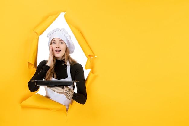 Vista frontal cocinera sosteniendo sartén negro sobre amarillo emoción sol comida foto trabajo cocina cocina color