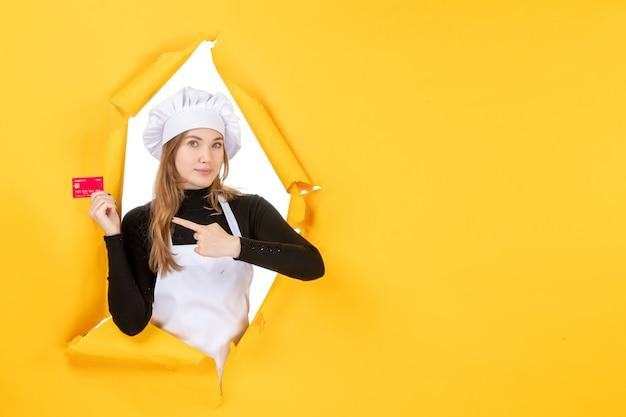 Vista frontal cocinera sosteniendo una tarjeta bancaria roja en color amarillo dinero foto de trabajo cocina cocina emoción comida