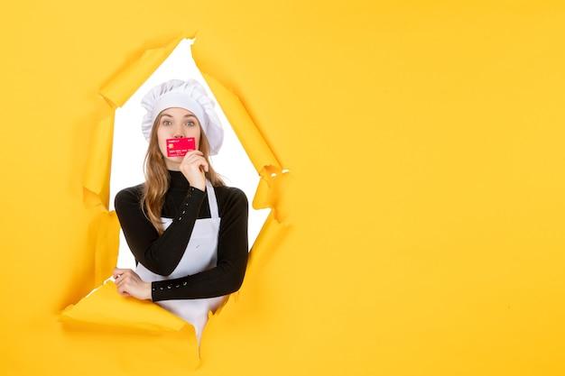Vista frontal cocinera sosteniendo una tarjeta bancaria roja en color amarillo dinero foto de trabajo comida cocina emoción