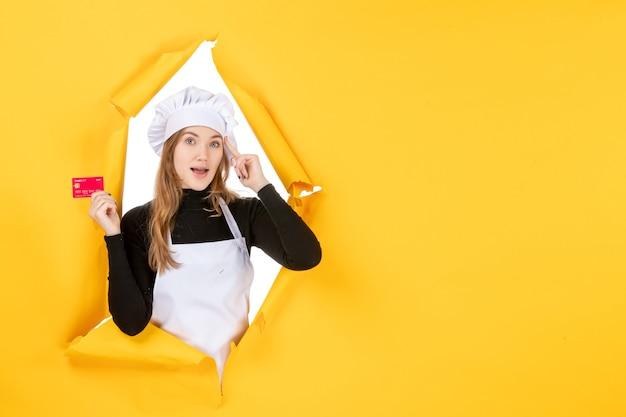 Vista frontal cocinera sosteniendo una tarjeta bancaria roja en color amarillo dinero trabajo cocina cocina emoción comida