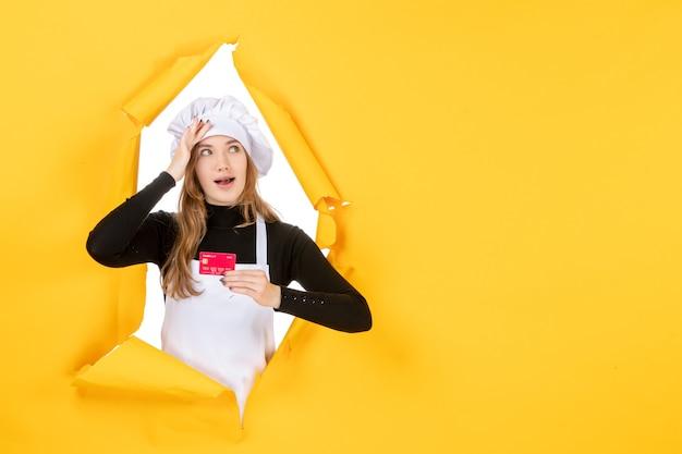 Vista frontal cocinera sosteniendo una tarjeta bancaria roja sobre amarillo foto emoción dinero cocina cocina trabajo de color