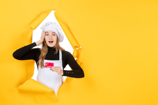 Vista frontal cocinera sosteniendo tarjeta bancaria roja sobre amarillo foto de trabajo emoción comida cocina color dinero cocina