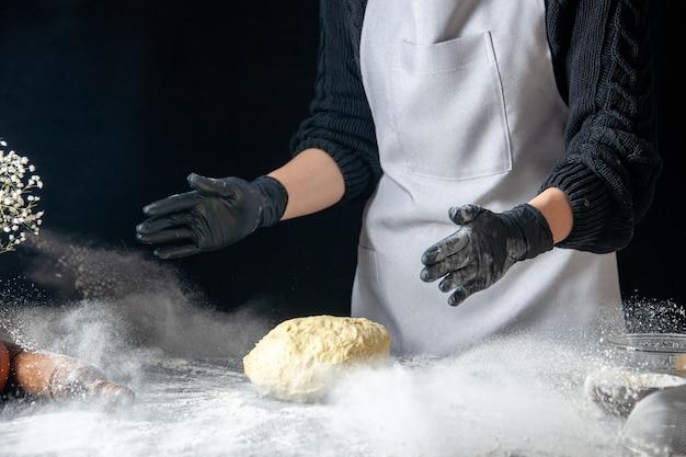 Vista frontal cocinera tirando la masa en la harina blanca sobre la masa oscura huevo trabajo panadería hotcake pastelería cocina cocina