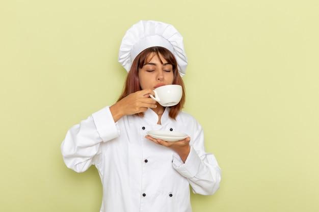 Vista frontal cocinera en traje de cocinero blanco bebiendo té en superficie verde