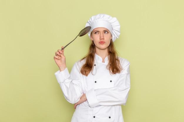 Vista frontal de la cocinera en traje de cocinero blanco sosteniendo una cuchara de plata grande pensando en la pared verde