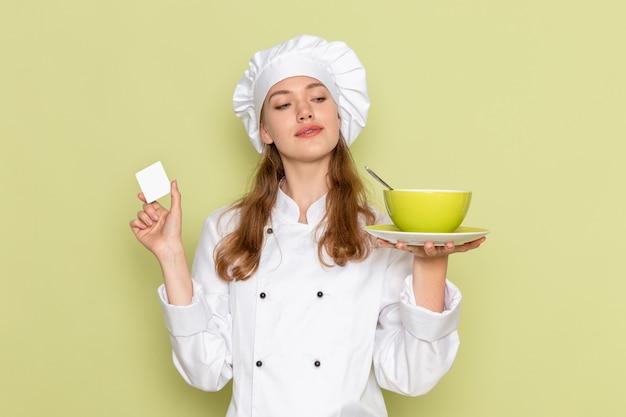 Vista frontal de la cocinera en traje de cocinero blanco sosteniendo placa verde en la pared verde