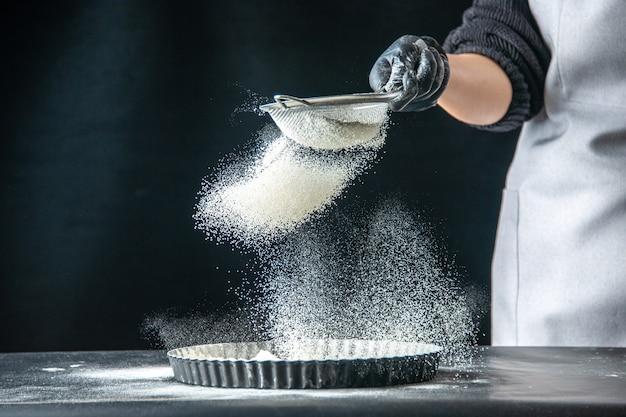 Vista frontal cocinera vertiendo harina blanca en la sartén en un huevo oscuro trabajo panadería hotcake pastelería cocina masa de cocina
