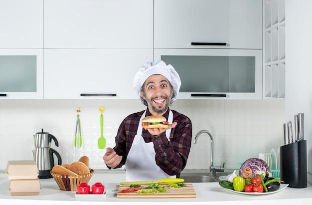 Vista frontal del cocinero macho sosteniendo una sabrosa hamburguesa de pie detrás de la mesa de la cocina