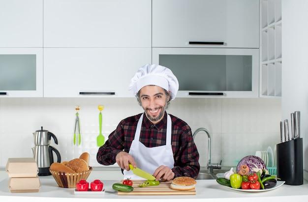 Vista frontal del cocinero masculino cortando pimientos en la cocina