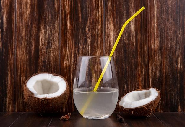 Vista frontal de cocos a la mitad y frescos con un vaso de agua sobre una superficie de madera