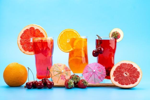 Vista frontal de un cóctel de frutas frescas con frutas rojas frescas y cítricos, enfriamiento con hielo en azul, cóctel de jugo de bebida color de fruta