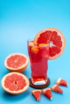 Una vista frontal de cóctel de frutas frescas con rodajas de frutas frescas enfriamiento con hielo en azul, cóctel de jugo de bebida color de fruta