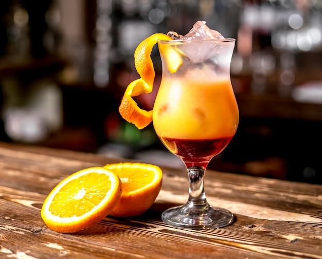 Vista frontal cóctel con rodajas de naranja y decoración de cáscara de naranja