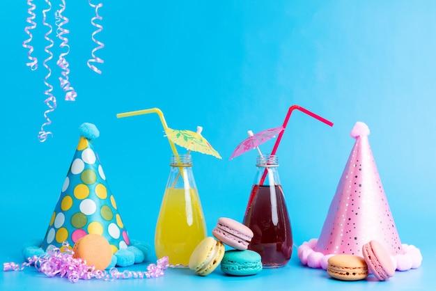 Una vista frontal de cócteles de colores refrescantes con pajitas junto con macarons franceses y coloridas gorras de cumpleaños en azul