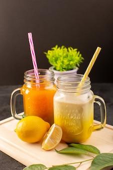 Una vista frontal cócteles fríos coloreados dentro de latas de vidrio con pajitas de colores, limones, hojas verdes en el escritorio de madera y crema oscuro