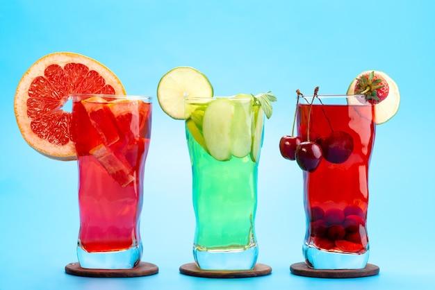 Una vista frontal de cócteles de frutas frescas con rodajas de fruta fresca enfriamiento con hielo en azul, cóctel de jugo de bebida color de fruta