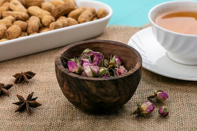 Vista frontal de cogollos secos con una taza de té y maní