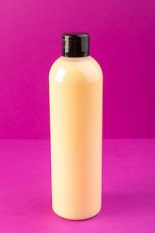 Una vista frontal de color crema botella de champú de plástico puede con tapa negra aislada en el fondo púrpura cosméticos belleza cabello