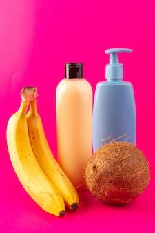 Una vista frontal de color crema botella de champú de plástico puede con tapa negra aislada junto con plátanos tubo azul y nuez de coco en el fondo de color rosa cosméticos belleza cabello