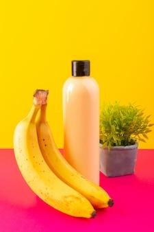 Una vista frontal de color crema botella de champú de plástico puede con tapa negra aislada con plátanos y pequeña planta en el fondo rosa-amarillo cosméticos belleza cabello
