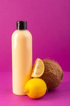 Una vista frontal de color crema botella de champú de plástico puede con tapa negra junto con limones y coco aislado en el fondo púrpura cosméticos belleza cabello
