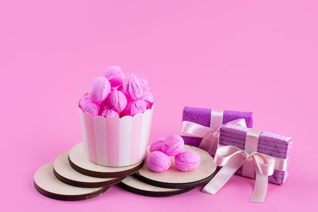 Una vista frontal de color rosa, galletas deliciosas y deliciosas junto con cajas de regalo de color púrpura en rosa, galleta de galleta de azúcar dulce