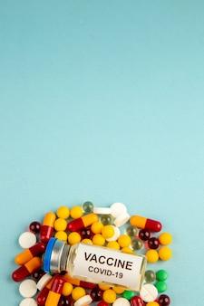 Vista frontal de coloridas píldoras con vacuna sobre la superficie azul color salud covid- laboratorio de ciencia del virus del hospital pandémico