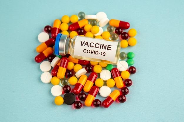 Vista frontal de coloridas píldoras con vacuna en la superficie azul hospital de salud de color covid- laboratorio de ciencias pandemia de virus de drogas